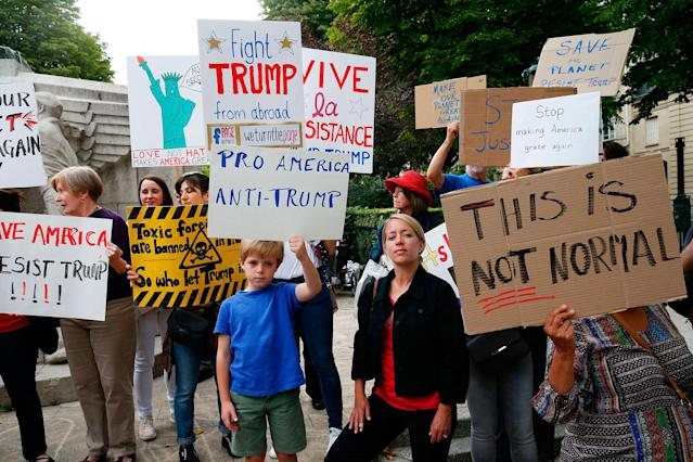 <p>Protesters hold a placard reading 'Pro America – Anti-Trump' as they gather at the Memorial to the American volunteers at the Place des Etats-Unis in Paris, on July 13, 2017, to demonstrate against the visit of President Donald Trump. (Photo: Geoffroy Van Der Hasselt/AFP/Getty Images) </p>
