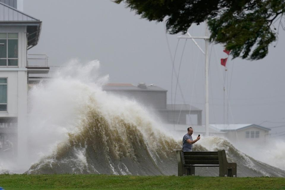 A man takes pictures of high waves along the shore of Lake Pontchartrain as Hurricane Ida nears, Sunday, Aug. 29, 2021, in New Orleans. (AP Photo/Gerald Herbert) (Copyright 2021 The Associated Press. All rights reserved.)