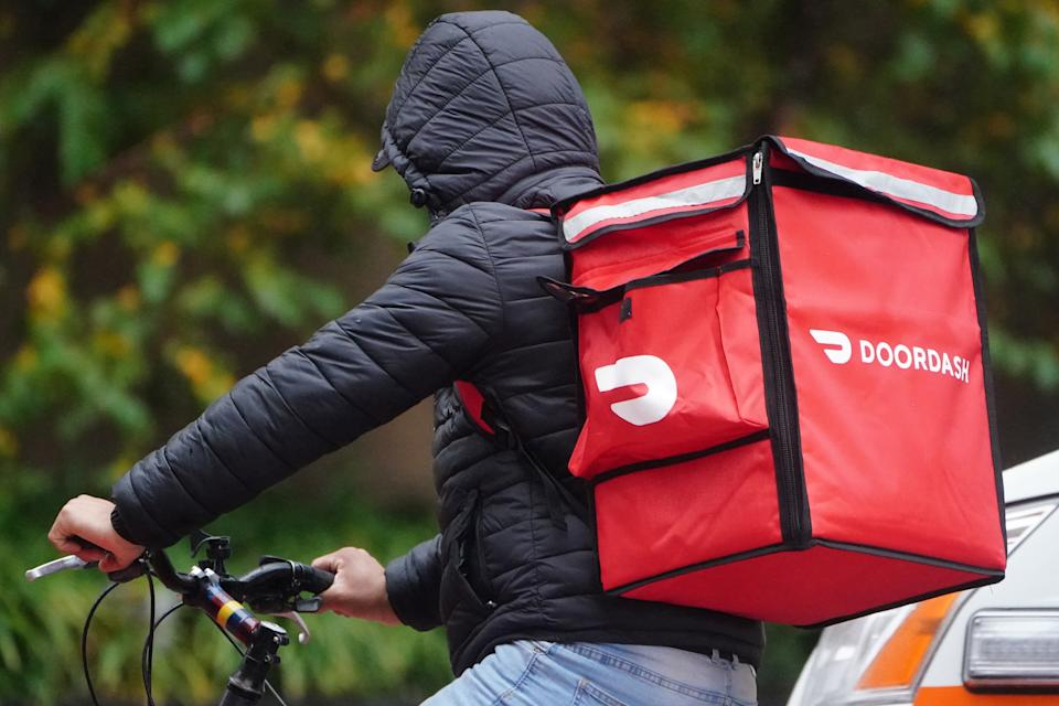A delivery person for Doordash rides his bike in the rain during the coronavirus disease (COVID-19) pandemic in the Manhattan borough of New York City, New York, U.S., November 13, 2020. REUTERS/Carlo Allegri