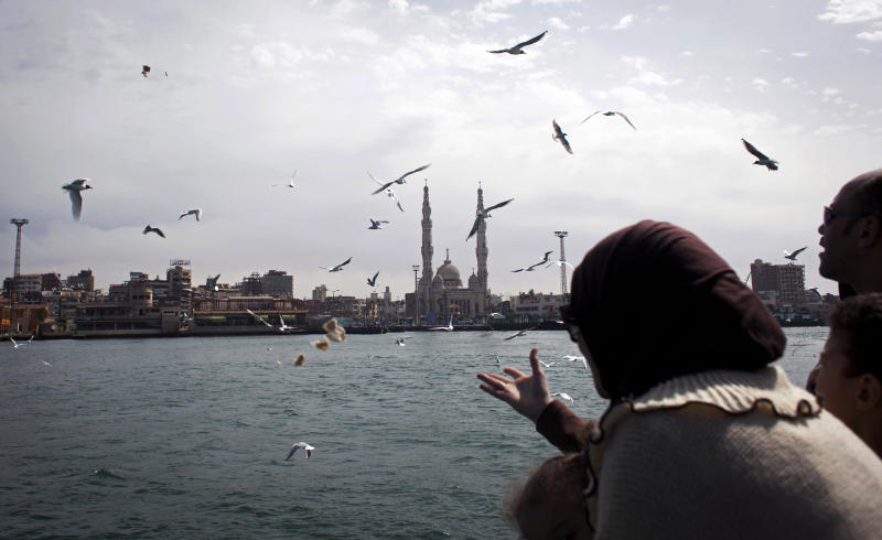 An Egyptian family feeds seagulls while crossing the Suez Canal aboard a ferry during a general strike, in Port Said, Egypt, Friday, Feb. 22, 2013. In the restive city of Port Said, where a general strike entered its sixth day on Friday, factory workers, activists and laborers have held street rallies that brought the coastal city on the northern tip of the Suez Canal to a halt, though shipping in the international waterway has not been affected. (AP Photo/Nasser Nasser)
