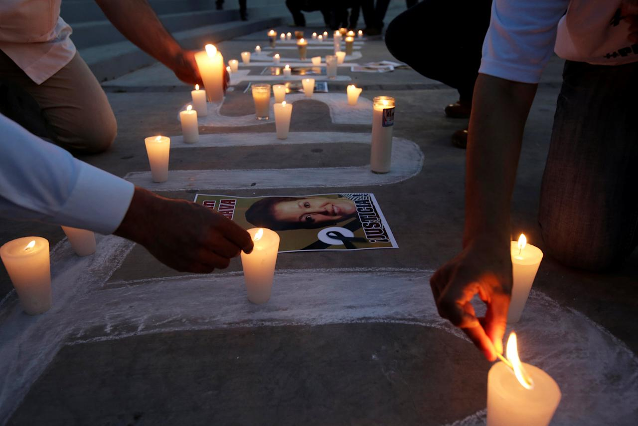 Journalists light candles during a protest to mark the first anniversary of the murder of their colleague Miroslava Breach, outside the state government offices in Ciudad Juarez, Mexico March 22, 2018. REUTERS/Jose Luis Gonzalez