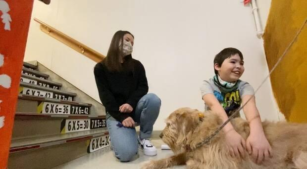 Brentt Linville, in Grade 2, stops to pet Luna while walking through the school with educational assistant Laura Pipietro. (Philippe Morin/CBC - image credit)