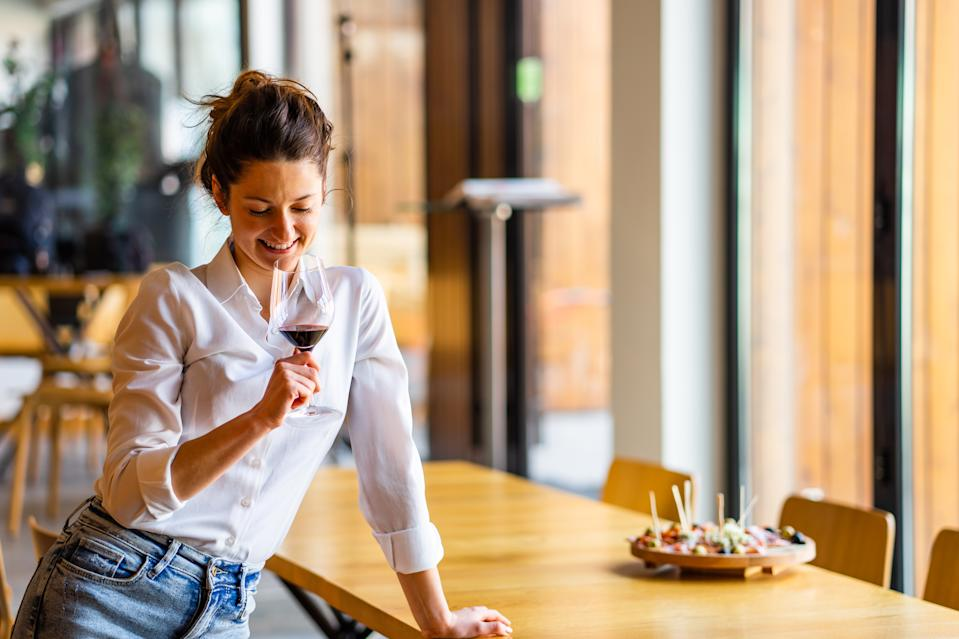 Woman Looking At Wineglass While Standing By Table