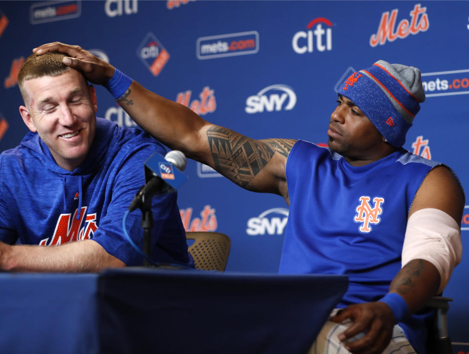 New York Mets left fielder Yoenis Cespedes, right, rubs Todd Frazier's hair during a new conference at Citi Field, Wednesday, March 28, 2018, in New York, a day before the team's opening day. Cespedes said he felt the Mets' 2018 team is better than the team they had in 2015, which went to the World Series. (AP Photo/Kathy Willens)