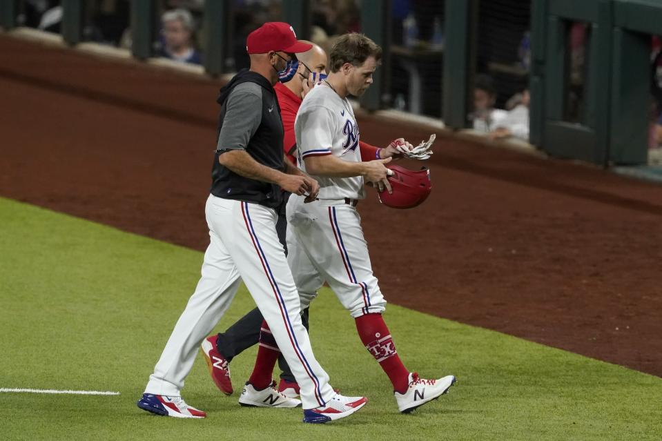 Texas Rangers manager Chris Woodward, left, and a member of the team's staff, rear, escort Brock Holt, right, off the field after Holt hit a single that scored Nick Solak during the eighth inning of the team's baseball game against the Toronto Blue Jays in Arlington, Texas, Tuesday, April 6, 2021. Holt left the game with an unknown injury. (AP Photo/Tony Gutierrez)