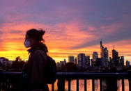 A woman wearing a face mask walks over a bridge with the buildings of the banking district in background in Frankfurt, Germany, Monday, Oct. 26, 2020. (AP Photo/Michael Probst)