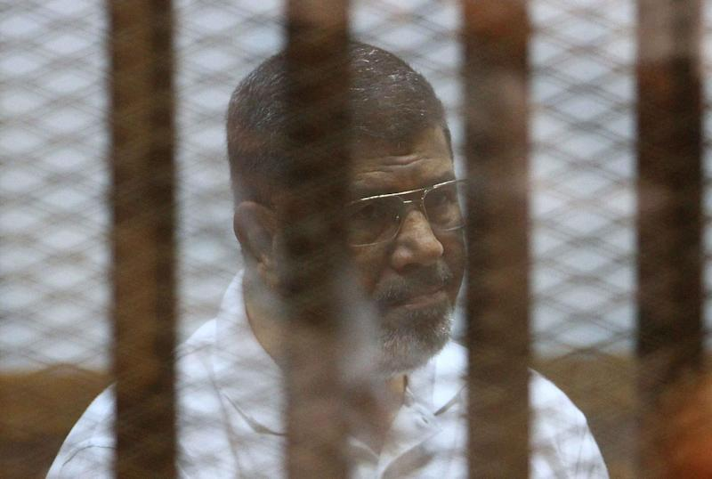 Egypt's deposed Islamist president Mohamed Morsi, previously charged along with 130 others of plotting attacks and escaping from prison in 2011, sits inside the defendant's cage during his trial at the police academy in Cairo on August 18, 2014