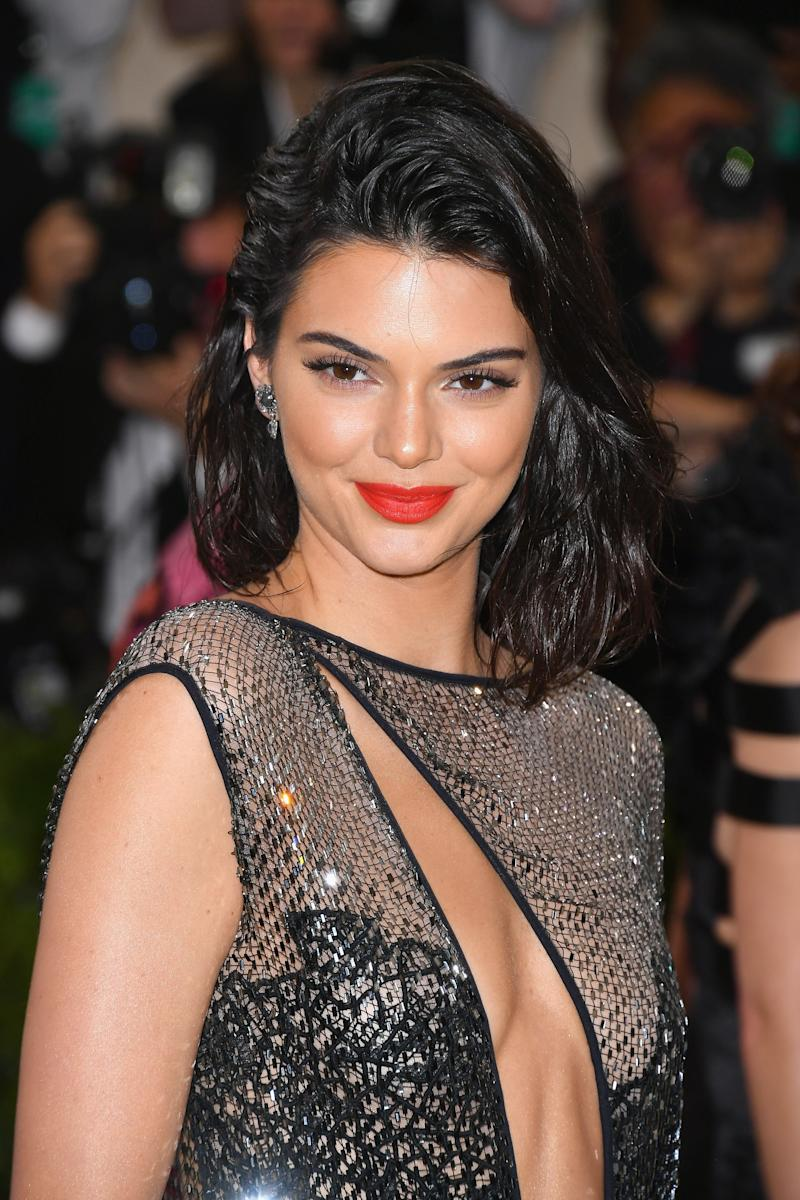 At the 2017 Costume Institute Gala, Kendall Jenner's makeup features a bold coral lip that pairs beautifully with her sleek wet waves.