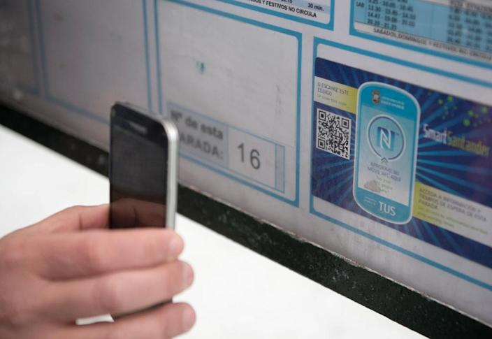 A resident uses a mobile phone to read a QR code on a public bus stop in Santander (AFP Photo/Ander Gillenea)