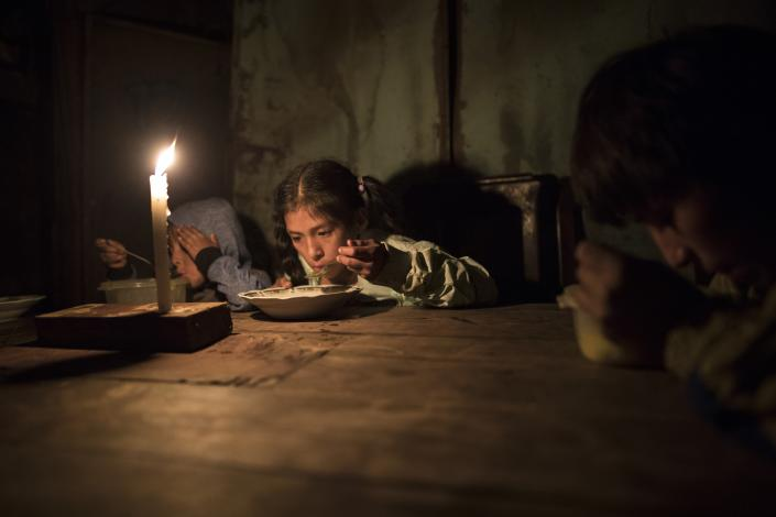 FILE - In this Monday, June 8, 2020 file photo Siblings Estiben Aquiño, 4, Estefany Aquino, 11, and Javier Aquino, 14, eat dinner illuminated by a candle in their home in the Nueva Esperanza neighborhood that has no access to electricity, in Lima, Peru. (AP Photo/Rodrigo Abd, File)