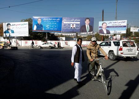 An Afghan man rides on his bicycle in front of election posters of parliamentarian candidates ahead of the elections in Kabul, Afghanistan October 18, 2018. REUTERS/Omar Sobhani