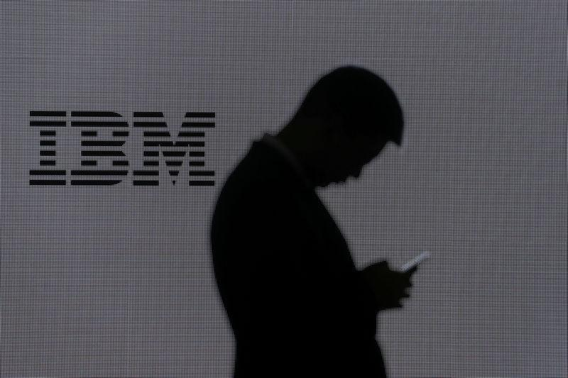 FILE PHOTO: A man checks his mobile phone outside IBM's booth at the Mobile World Congress in Barcelona