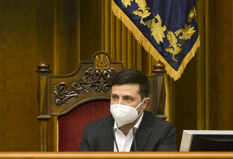 Ukrainian President Volodymyr Zelenskiy wearing a face mask to protect against coronavirus speaks during an extraordinary parliamentary session in Kyiv, Ukraine, Monday, March 30, 2020. Ukraine has been under quarantine since March 12. The new coronavirus causes mild or moderate symptoms for most people, but for some, especially older adults and people with existing health problems, it can cause more severe illness or death. (AP Photo)