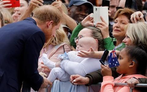 Father-to-be, the Duke of Sussex, is greeted by a baby among the crowd - Credit: Getty Images