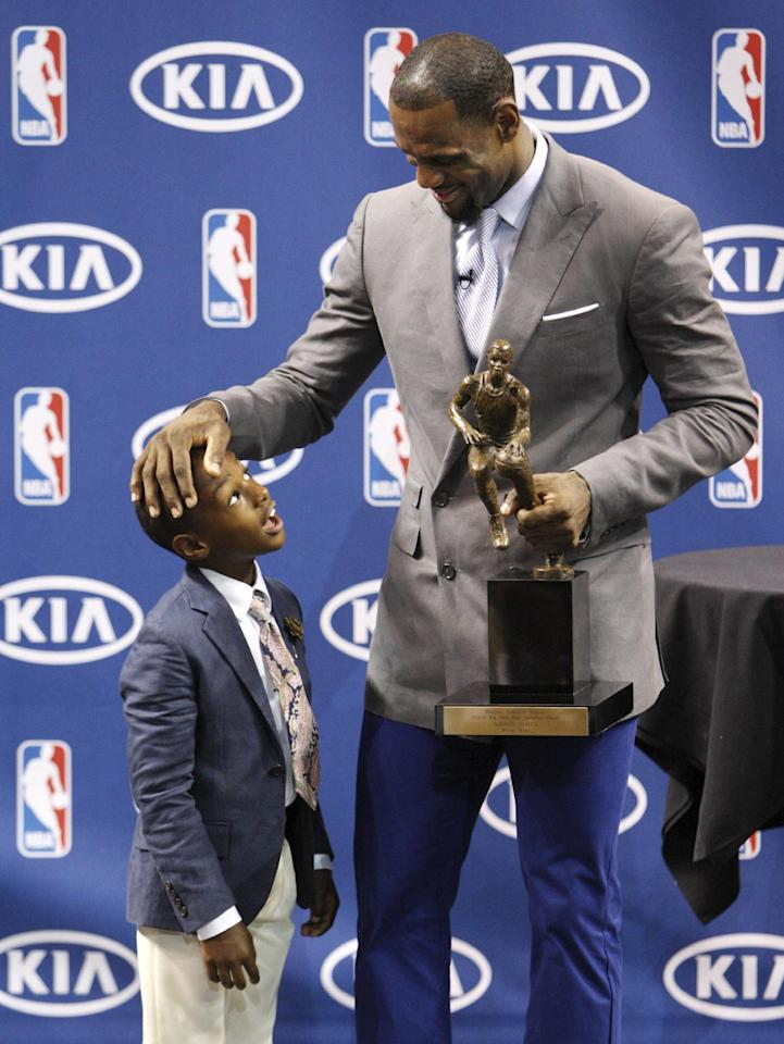 "Miami Heat's LeBron James, right, chats with his son LeBron James Jr. after having accepted the NBA MVP trophy, Saturday, May 12, 2012, in Miami. Calling the honor ""overwhelming"" but pointing to a ""bigger goal,"" James on Saturday became the eighth player in NBA history to win the MVP award three times. (AP Photo/Wilfredo Lee)"