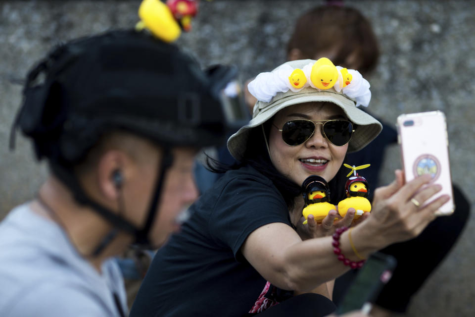 A protester takes a selfie with yellow ducks, which have become good-humored symbols of resistance during anti-government rallies, on Wednesday, Nov. 25, 2020, in Bangkok, Thailand. Thai authorities have escalated their legal battle against the students leading pro-democracy protests, charging 12 of them with violating a harsh law against defaming the monarchy. (AP Photo/Wason Wanichakorn)