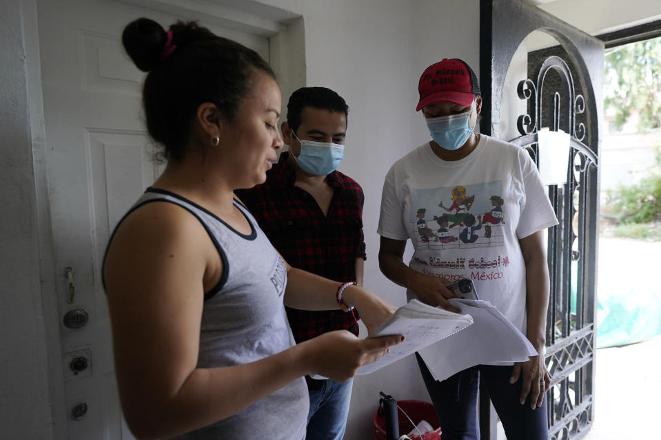 Sidewalk School founder Felicia Rangel-Samponaro, right, works with teacher Gabriela Fajardo, a 26-year-old Honduran seeking asylum in the United States, left, and assistant Victor Cavazos on Friday, Nov. 20, 2020, in Matamoros, Mexico. Like countless schools, the Sidewalk School went to virtual learning amid the coronavirus pandemic, but instead of being hampered by the change, it has blossomed. (AP Photo/Eric Gay)
