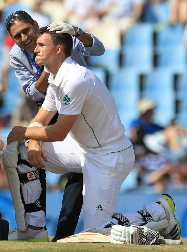 South Africa's batsman Ryan McLaren, front, is attended by an unidentified medic after being struck by a ball close to his right ear, from Australia's bowler Mitchell Johnson, on the fourth day of their their cricket test match at Centurion Park in Pretoria, South Africa, Saturday, Feb. 15, 2014. (AP Photo/ Themba Hadebe)