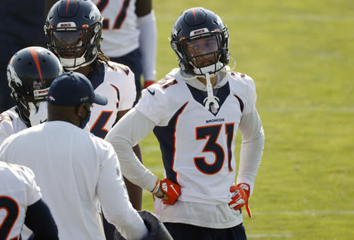 Denver Broncos safety Justin Simmons, right, listens to defensive backs coach Renaldo Hill during a break in drills at the team's NFL football training camp Friday, Aug. 14, 2020, in Englewood, Colo. (AP Photo/David Zalubowski)