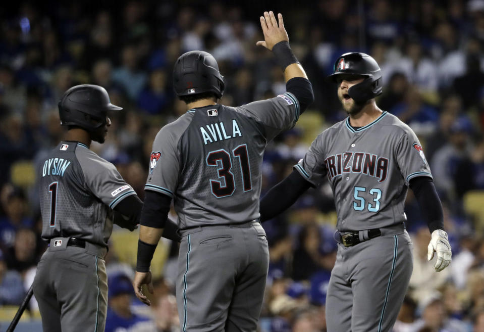 Arizona Diamondbacks' Christian Walker, right, is met at home plate by teammates Alex Avila and Jarrod Dyson after Walker's three-run home run against the Los Angeles Dodgers during the seventh inning of a baseball game Friday, March 29, 2019, in Los Angeles. (AP Photo/Marcio Jose Sanchez)