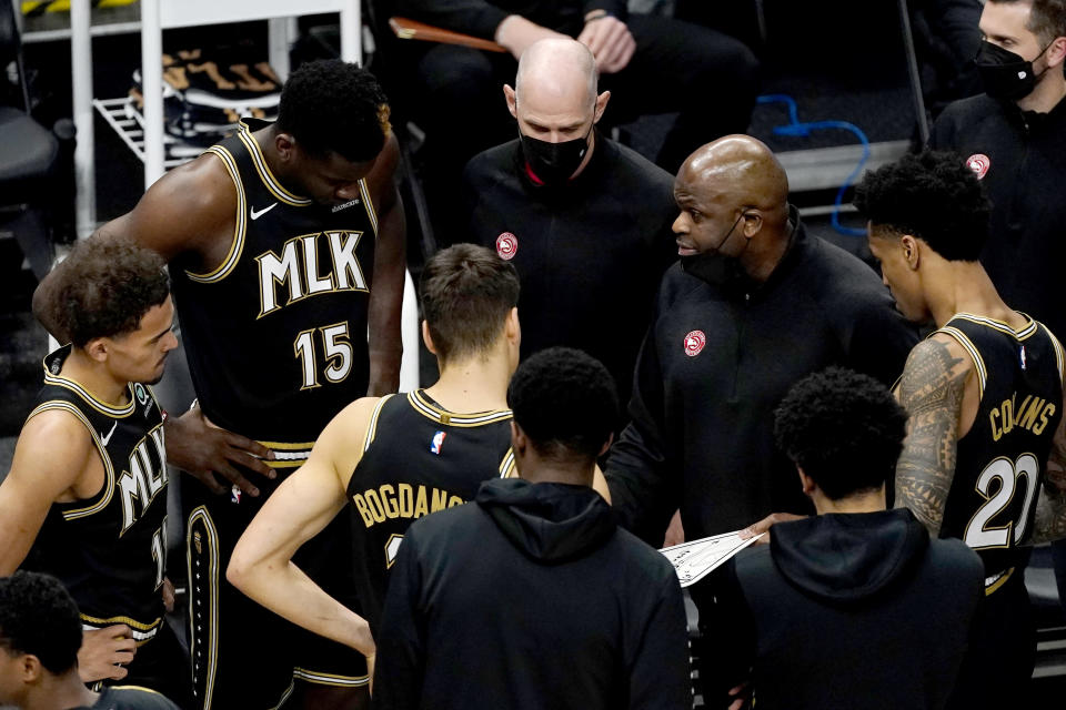 Atlanta Hawks head coach Nate McMillan, right, speaks to his player before an NBA basketball game against the Phoenix Suns, Wednesday, May 5, 2021, in Atlanta. (AP Photo/John Bazemore)