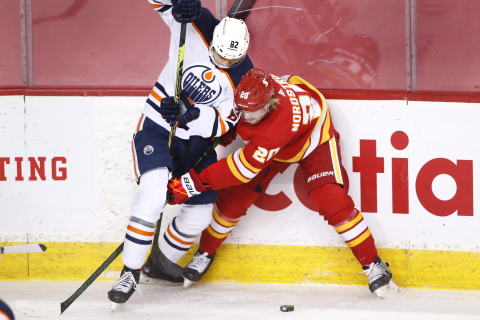 Edmonton Oilers' Caleb Jones, left, works for the puck against Calgary Flames' Joakim Nordstrom during the second period of an NHL hockey game Saturday, April 10, 2021, in Calgary, Alberta. (Larry MacDougal/The Canadian Press via AP)