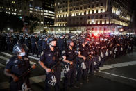 FILE — In his June 4, 2020 file photo, New York City Police Department officers stand in formation after arresting multiple protesters marching after curfew on Fifth Avenue, in New York, following the death of George Floyd, in Minneapolis. The New York Police Department was caught off guard by the size and scope of the spring protests sparked by the police killing of George Floyd in Minneapolis and resorted to disorder control tactics that stoked tensions and stifled free speech rights, the city's inspector general said in a report released Friday, Dec. 18, 2020. (AP Photo/John Minchillo, File)