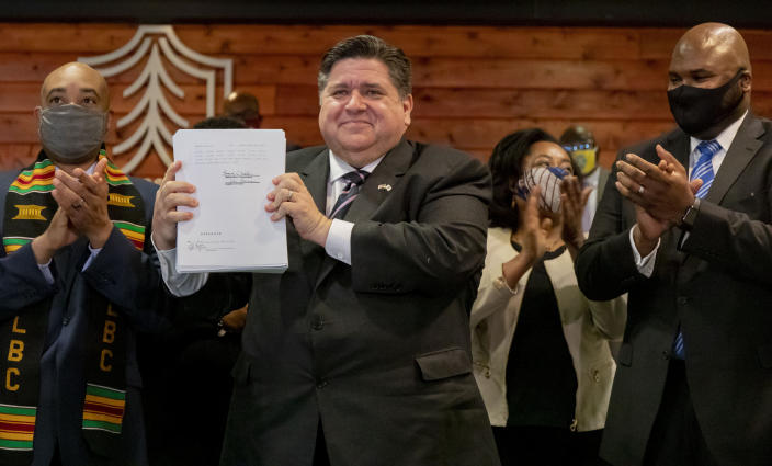 Illinois Gov. J.B. Pritzker is joined by lawmakers and community advocates including state Rep. Justin Slaughter, left, and state Sen. Elgie Sims Jr., right, as he signs HB 3653, a sweeping criminal justice and police reform bill, on Monday, Feb. 22, 2021 at Chicago State University. (Brian Cassella/Chicago Tribune via AP)