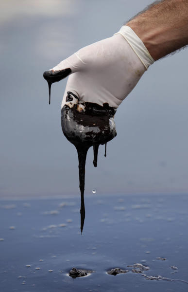 FILE - In this June 15, 2010 file photo, a member of Louisiana Gov. Bobby Jindal's staff wearing a glove reaches into thick oil on the surface of the northern regions of Barataria Bay in Plaquemines Parish, La. Over BP's objections, a federal appeals court on Friday Jan. 10, 2014, upheld a judge's approval of the company's multibillion-dollar settlement with lawyers for businesses and residents who claim the massive 2010 oil spill in the Gulf of Mexico cost them money. (AP Photo/Gerald Herbert, File)