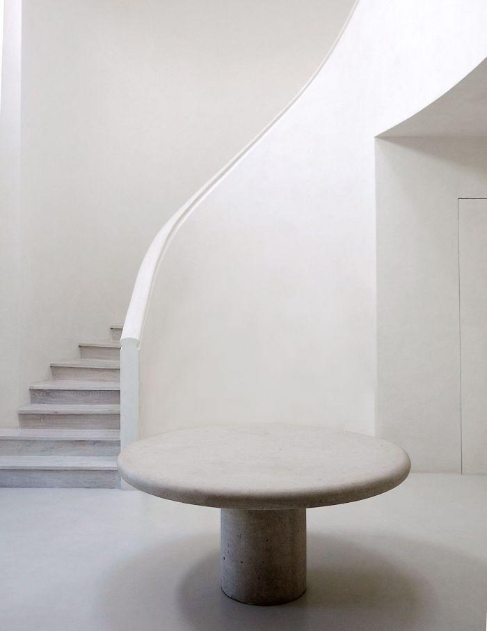 A sleek spiral staircase and round table in Kim and Kayne's all-white LA mansion.