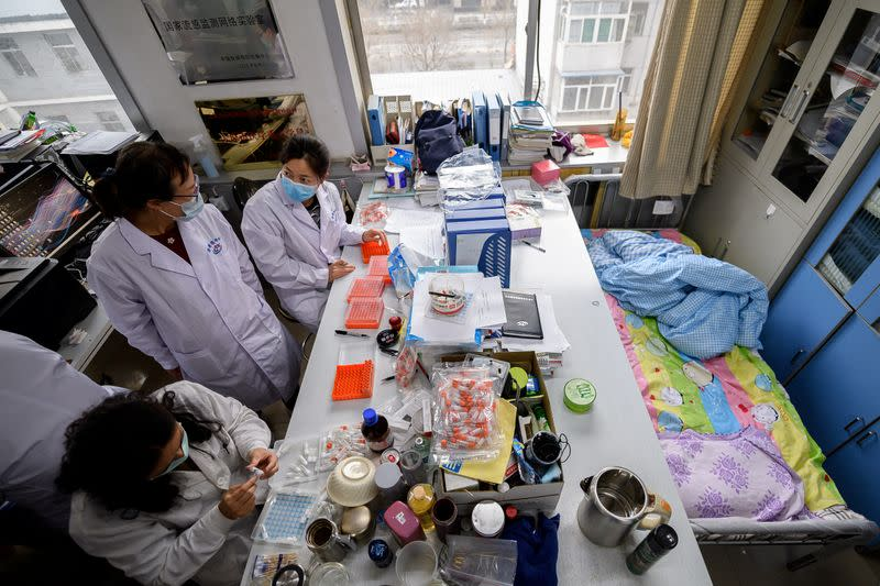 Workers are seen next to a bed placed inside an office at a centre for disease control and prevention, as the country is hit by an outbreak of the novel coronavirus, in Taiyuan