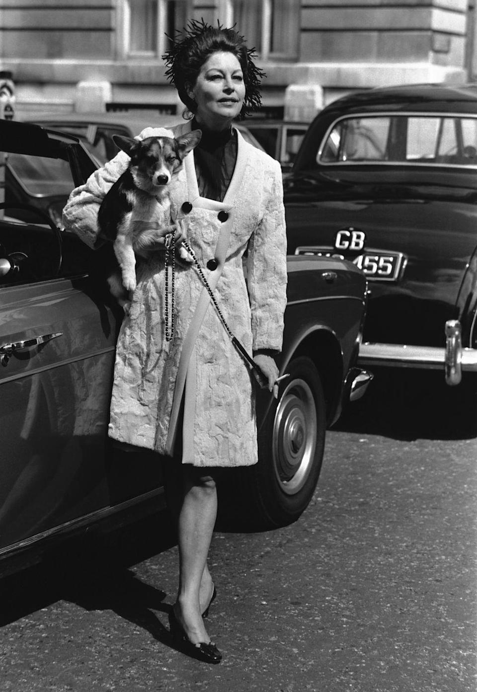 <p>Photographed in London where she moved in the late 1960s and remained until her death in 1990, Gardner poses on a street with one of her corgis in a fabulously cut overcoat. </p>