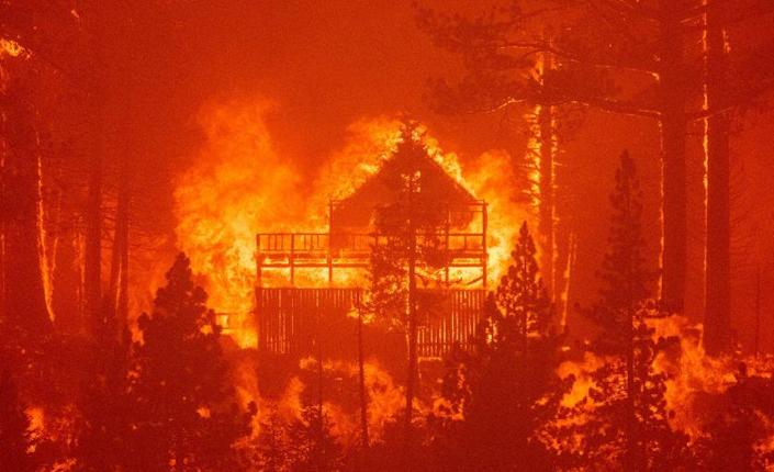 Flames consume multiple homes as the Caldor fire pushes into South Lake Tahoe, California on August 30, 2021. - At least 650 structures have burned and thousands more are threatened as the Caldor fire moves into the resort community of South Lake Tahoe, California. Thousands of people were ordered to evacuate Monday as a huge wildfire loomed over a major US tourist spot, filling the air with choking smoke. The Caldor Fire has already torn through more than 270 square miles (700 square kilometers), razing hundreds of buildings. (Photo by JOSH EDELSON / AFP) (Photo by JOSH EDELSON/AFP via Getty Images)