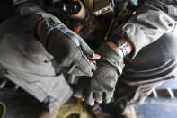 """U.S. Marine Cpl. Thalles Souza, a crew chief on a VM-22 Osprey, with VMM-266, """"Fighting Griffins,"""" from Marine Corps Air Station New River, from Jacksonville, N.C., adjusts his gloves en route to Toussaint Louverture International Airport, Saturday, Aug. 28, 2021, in Port-au-Prince, Haiti. A 7.2 magnitude earthquake on Aug. 22, caused heavy damage to the country. (AP Photo/Alex Brandon)"""