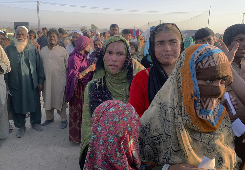 Afghan families gather to receive food stuff distributing by an Islamabad-based Christian organization on the outskirts of Chaman, a border town in the Pakistan's southwestern Baluchistan province, Tuesday, Aug. 31, 2021. Dozens of Afghan families have crossed into Pakistan through the southwestern Chaman border a day after the U.S. wrapped up its 20-year military presence in the Taliban-controlled country. (AP Photo)