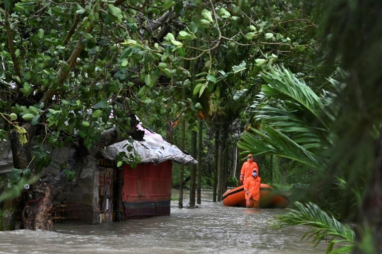 Personnel from India's National Disaster Response Force (NDRF) use inflatable boats to ferry stranded villagers through the flood waters
