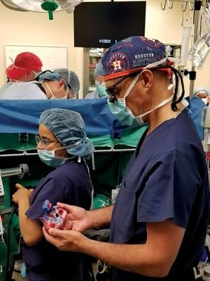 Dr. Salazar references the patient-specific anatomical heart model outside of the sterile field in the operating room.