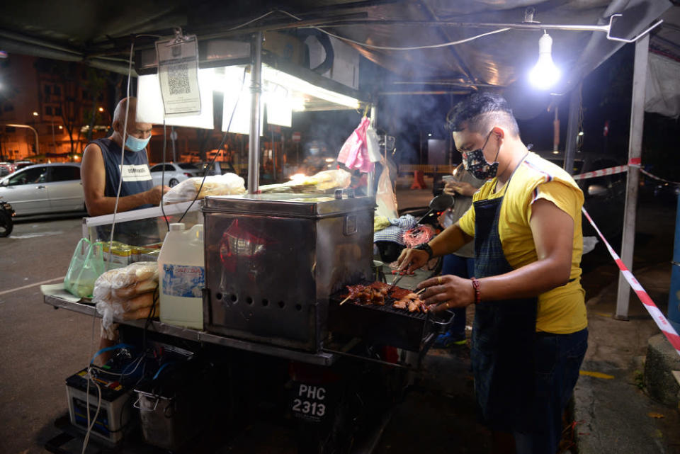 Tan Boon grilling the orders for customers during his night session in Air Itam.