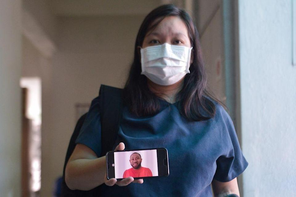 Simon Momoh's wife, Low Kar Hui, shows a picture of her husband on her phone at the Shah Alam High Court April 21, 2021. — Picture by Miera Zulyana