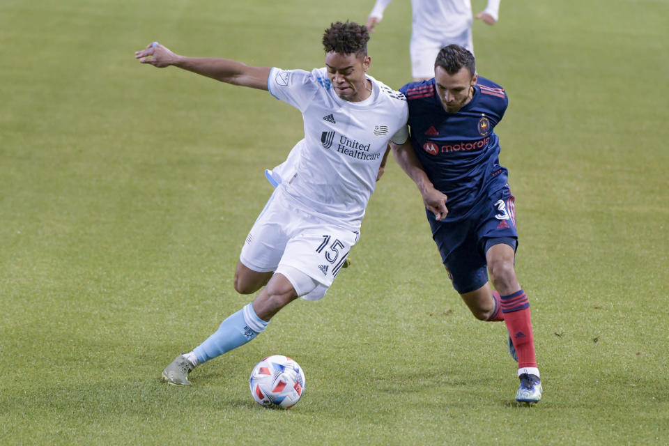 New England Revolution midfielder Brandon Bye (15) and Chicago Fire defender Jonathan Bornstein (3) work for control of the ball during the first half of an MLS soccer match in Chicago, Saturday, April 17, 2021. (AP Photo/Mark Black)