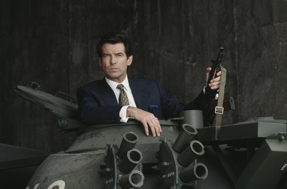 Irish actor Pierce Brosnan poses in the hatch of a Russian T55 Main Battle Tank holding a Kalashnikov automatic rifle, in a publicity still for the James Bond film 'GoldenEye', 1995. (Photo by Keith Hamshere/Getty Images)