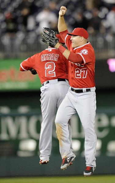 Los Angeles Angels center fielder Mike Trout (27) celebrates with teammate Erick Aybar (2) after a 4-2 win over the Washington Nationals with Erick Aybar (2) in a baseball game, Monday, April 21, 2014, in Washington. (AP Photo/Nick Wass)