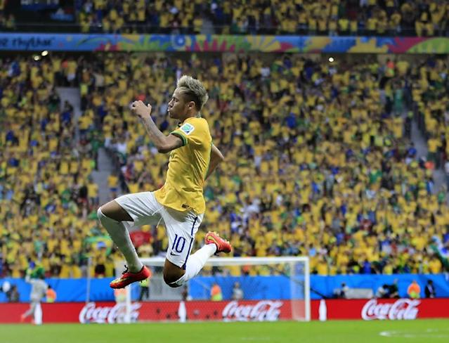 Brazil's Neymar leaps in the air to celebrate after scoring his side's second goal during the group A World Cup soccer match between Cameroon and Brazil at the Estadio Nacional in Brasilia, Brazil, Monday, June 23, 2014. (AP Photo/Bernat Armangue)