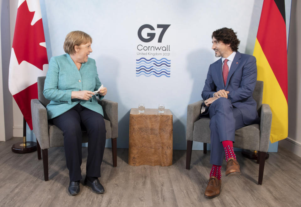 Canadian Prime Minister Justin Trudeau, right, speaks with German Chancellor Angela Merkel at the start of a bilateral meeting at the G7 Summit in Carbis Bay, Cornwall, England, Saturday, June 12, 2021. (Adrian Wyld/The Canadian Press via AP)