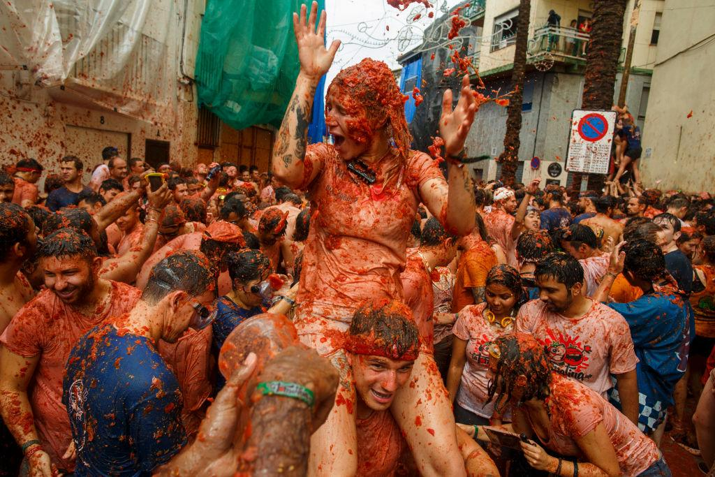 <p>Revellers enjoy the atmosphere in tomato pulp while participating the annual Tomatina festival in Bunol, Spain. An estimated 22,000 people threw 150 tonnes of ripe tomatoes in the world's biggest tomato fight held annually in this Spanish Mediterranean town. (Photo by Pablo Blazquez Dominguez/Getty Images) </p>