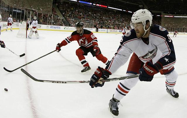 In this photograph taken with a fisheye lens, Columbus Blue Jackets defenseman David Savard, right, passes the puck as New Jersey Devils right wing Jaromir Jagr (68), of Czech Republic, tries to intercept the pass during the second period of an NHL hockey game, Friday, Dec. 27, 2013, in Newark, N.J. (AP Photo/Julio Cortez)