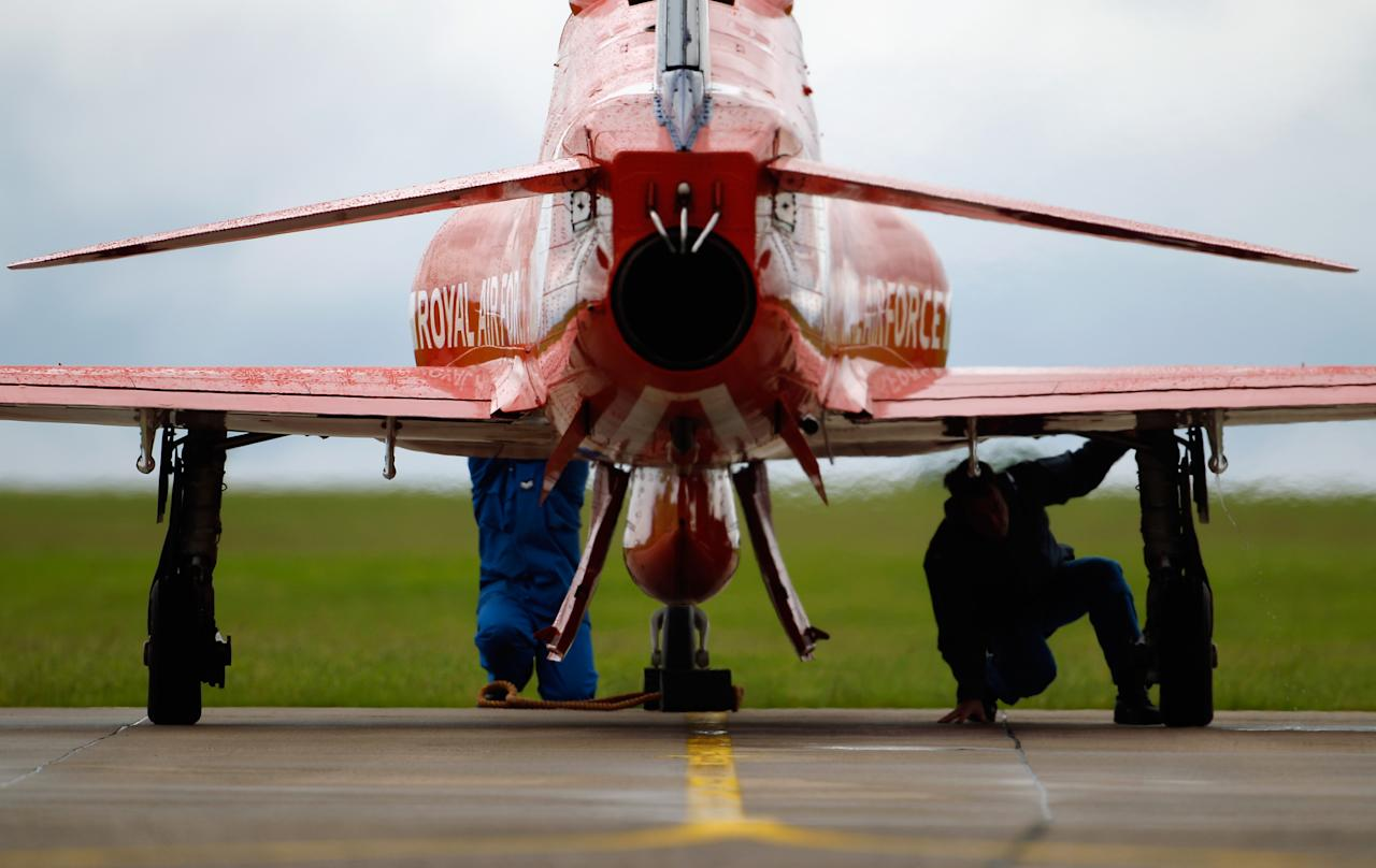 SCAMPTON, ENGLAND - JUNE 22:  Ground crew carry out pre-flight checks before take off as The Red Arrows practice their 2012 air display at RAF Scampton on June 22, 2012 in Scampton, England. The famous Royal Air Force Red Arrows are perfecting their routine for a fly past next week when the Olympic torch arrives in Norfolk and also for an audience of millions during the opening ceremony of the London 2012 Olympics.  (Photo by Christopher Furlong/Getty Images)