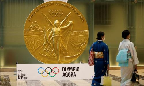Women walk past a large-scale reproduction of Tokyo 2020 Olympic Games medal
