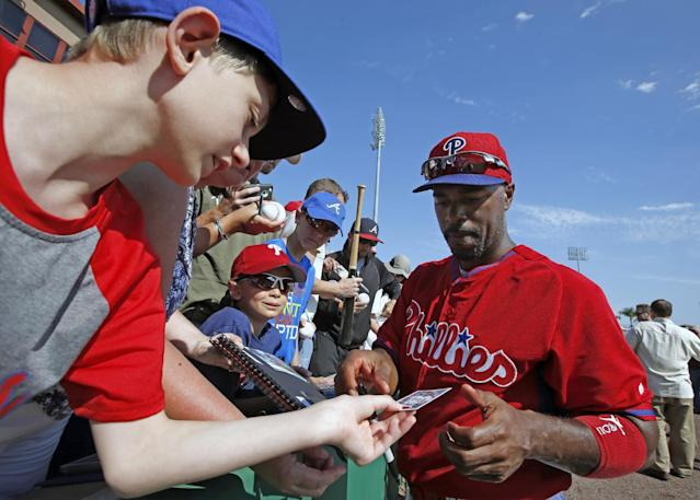 Philadelphia Phillies' Jimmy Rollins, right, autographs a baseball trading card for a young fan before a spring exhibition baseball game in Clearwater, Fla., Monday, March 10, 2014. (AP Photo/Kathy Willens)