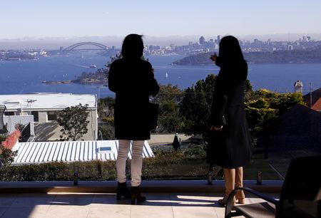 FILE PHOTO: The Sydney Opera House and Harbour Bridge can be seen behind a real estate agent and buyer in the Sydney suburb of Vaucluse, Australia